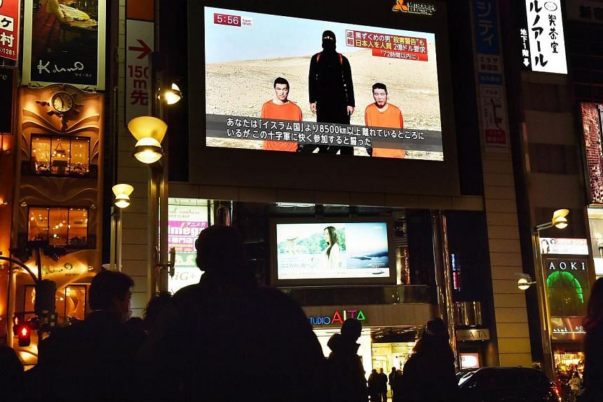 Passers-byon Jan 20, 2015,looking at a large TV screen in Tokyo broadcasting news reports about the two Japanese men (in orange) who have been kidnapped by ISIS. -- PHOTO: AFP