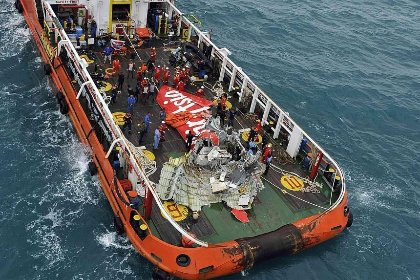 The tail of AirAsia QZ8501 passenger plane is seen on the deck of the Indonesian Search and Rescue (Basarnas) ship Crest Onyx after it was lifted from the sea bed, south of Pangkalan Bun, Central Kalimantan on Jan 10, 2015. -- PHOTO: REUTERS