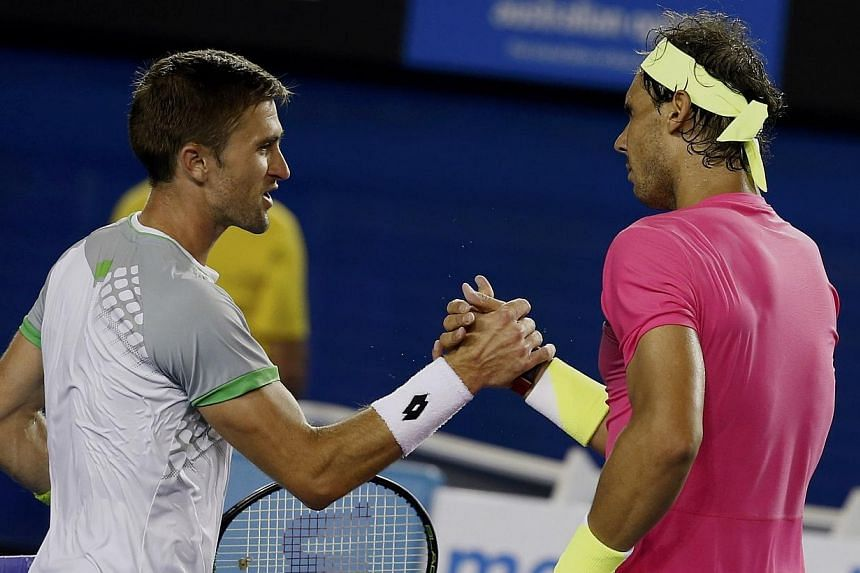 Rafael Nadal (right) of Spain shakes hands with Tim Smyczek of the US after defeating him in a gruelling five-setter during their men's singles second round match at the Australian Open 2015 tennis tournament in Melbourne on Jan 21, 2015. -- PHOTO: R