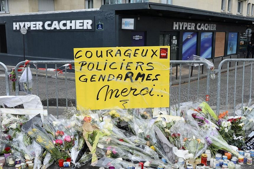 """Flowers, candles and a placard reading """"Brave Police officers, gendarmes, thank you"""" are found placed outside a Jewish supermarket on Jan 16, 2015,as a tribute to the victims of an attack by gunman Amedy Coulibaly.France has formally char"""
