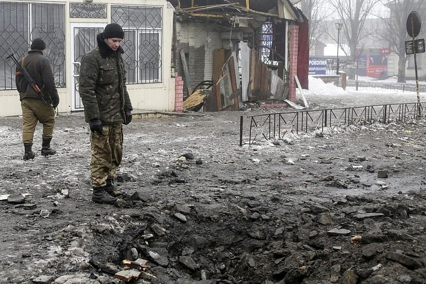 Ukrainian servicemen look at the craters from the shells at the central street of Debaltsevo, Ukraine on Jan 20, 2015. Russia is boosting its troop presence in eastern Ukraine and attacks from separatist rebels have intensified as they seek to g