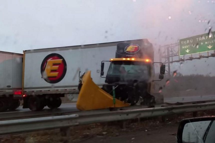 A tractor trailer stops just as it drives over a guard rail on the icy highway in New Jersey. -- SCREENGRAB: YOUTUBE