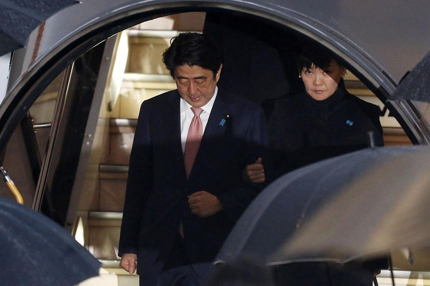 "Japan's Prime Minister Shinzo Abe (left) and his wife Akie disembark from a plane as they arrive at Haneda airport in Tokyo on Jan 21, 2015. Mr Abe said on Wednesday the government was in a ""race against time"" to save two Japanese nationals held host"