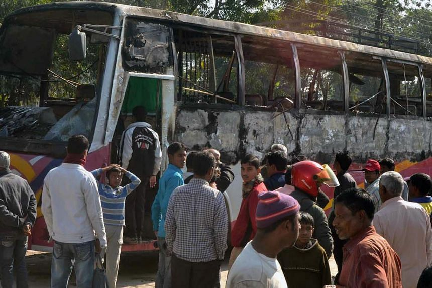 Onlookers surround the wreckage of a burnt bus allegedly set on fire by Bangladesh Nationalist Party (BNP) supporters during a blockade in Rangpur on Jan 14, 2015. Bangladesh security forces have arrested more than 7,000 opposition activists since th