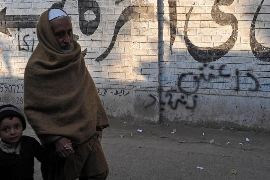 Pakistani pedestrians walk past wall graffiti (bottom) which reads Daesh, the arabic acronym for the Islamic State in Iraq and Syria (ISIS), in Peshawar on Nov 22, 2014.Pakistani security forces have arrested a man they believe is the commander