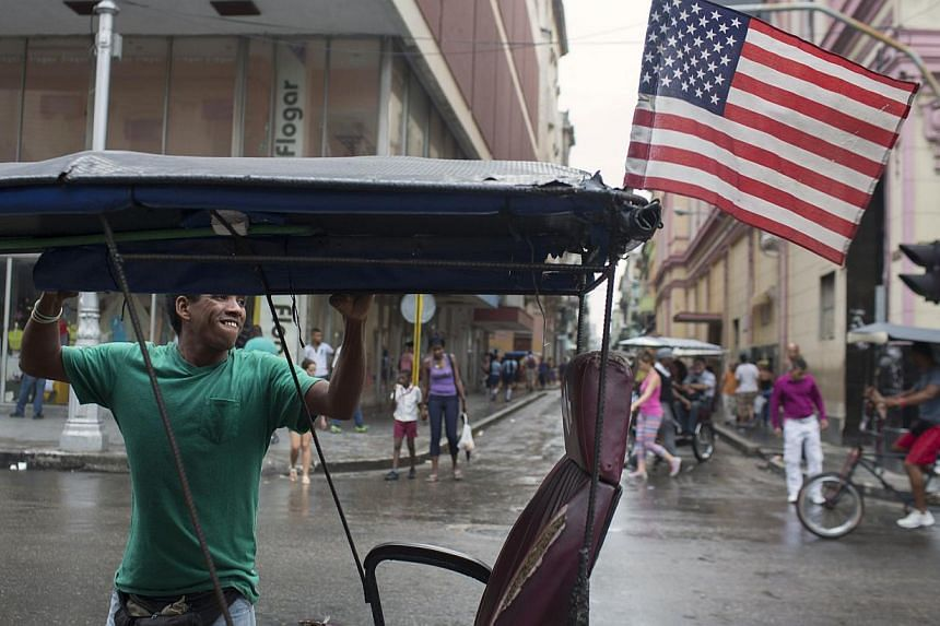 Bici taxi driver Yosvani Gomes, 39, lifts the curtains of his vehicle after a rain in downtown Havana Jan 20, 2015. The United States and Cuba opened two days of historic talks in Havana on Wednesday to end decades of Cold War-era animosity and