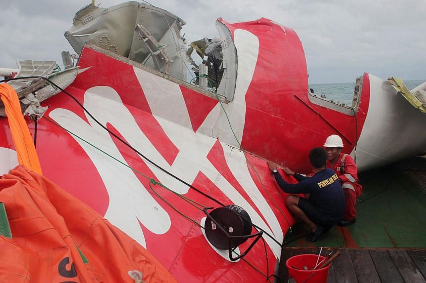An Indonesian diver and an official examine the wreckage from AirAsia flight QZ8501 after it was lifted into the Crest Onyx ship at sea on Jan 10, 2015. -- PHOTO: AFP