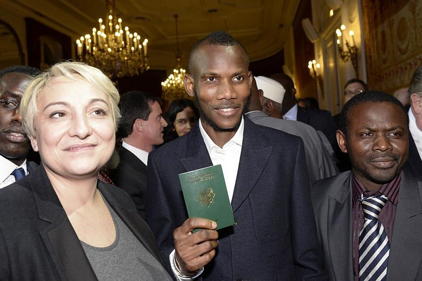 """Mr Lassana Bathily, a man of Malian origin described as a """"hero"""" after he helped hostages at a Jewish supermarket hide during last week's Paris attacks, holding his French passport following a ceremony on Jan 20, 2015at which was awarded French"""