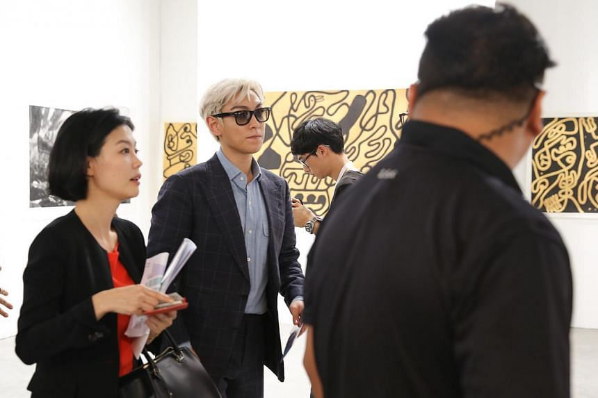 T.O.P of Korean boy band Big Bang viewing art works at Art Stage Singapore during a private viewing at the Marina Bay Sands Expo and Convention Centre on Jan 21, 2015.-- ST PHOTO:ONG WEE JIN
