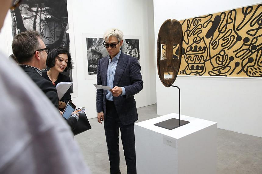 T.O.P of Korean boy band Big Bang viewing art works at Art Stage Singaporeduring a private viewing at the Marina Bay Sands Expo and Convention Centre on Jan 21, 2015.-- ST PHOTO:ONG WEE JIN