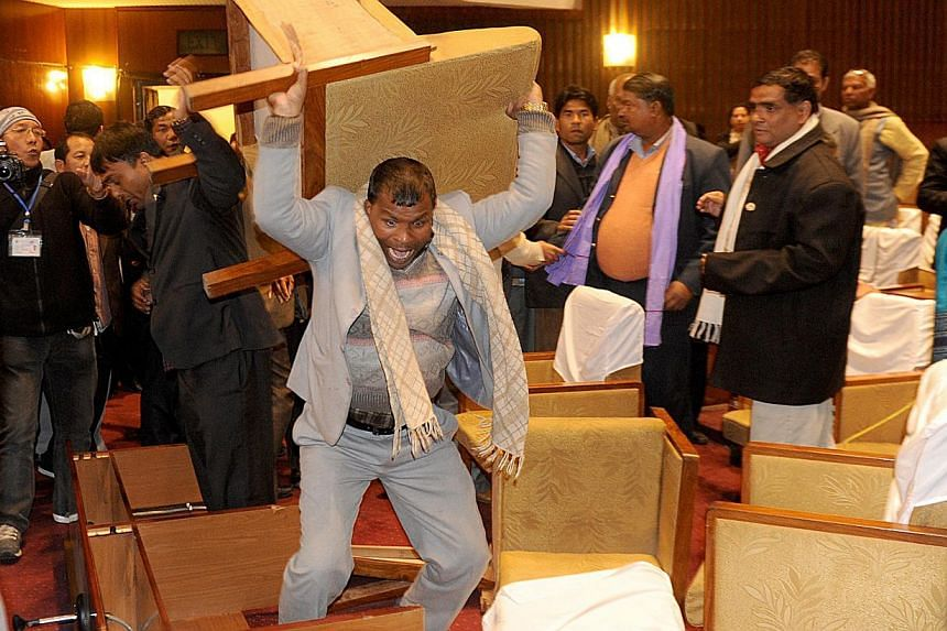 ANepalese constituent assembly member breaks a chair as tensions flare at a Parliament session in Kathmandu on Jan 20, 2015. The country's Maoist chief apologised on Wednesday, Jan 21, for his party's part in the scuffle that injured four secur