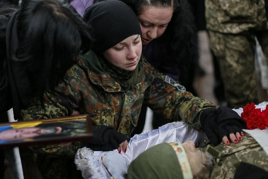 A woman reacting during a funeral ceremony for her father, a serviceman killed during fighting in the Lugansk region in eastern Ukraine, at Independence Square in central Kiev, Jan 20, 2015.Ukraine on Tuesday accused Russian forces of attacking