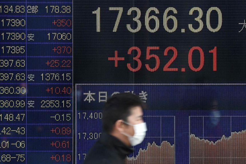 An electric quotation board flashing the Nikkei key index of the Tokyo Stock Exchange in front of a securities company in Tokyo on Jan 20, 2015. Asian shares held firm and the euro stayed under pressure on Wednesday as investors counted on the Europe