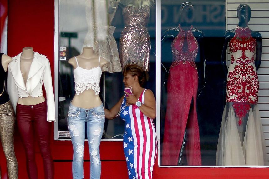 Ms Miriam Belarde looking at clothes for at a shop in Miami, Florida, on Dec 23, 2014. Last month's decline in US retail sales, the biggest in almost a year, suggests that Americans may be cautious about spending a windfall from cheaper petrol even a