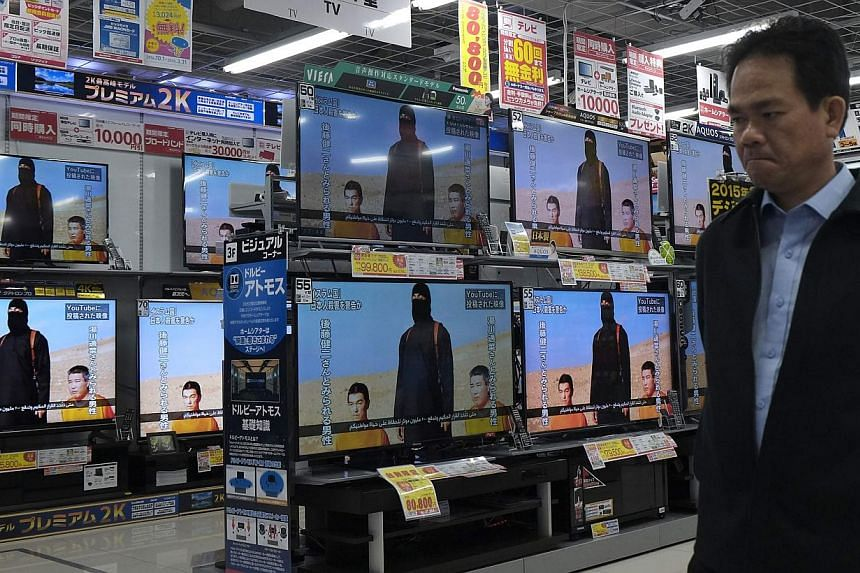 A man at an electronics store in Tokyo Jan 20, 2015,walking past television sets displaying a news programme about an ISIS video purporting to show two Japanese captives, Mr Kenji Goto and Mr Haruna Yukawa. -- PHOTO: REUTERS