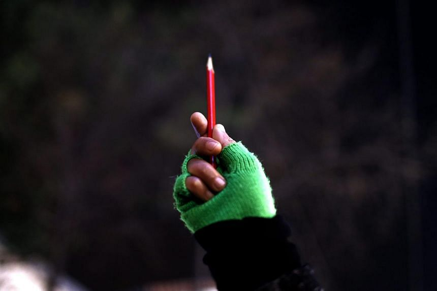 A woman holds a pencil outside the French Consulate in Istanbul, Turkey, Jan 8 2015, during a gathering to pay tribute to the victims of the Jan 7 attack on the Paris headquarters of French satirical magazine Charlie Hebdo. -- PHOTO: EPA