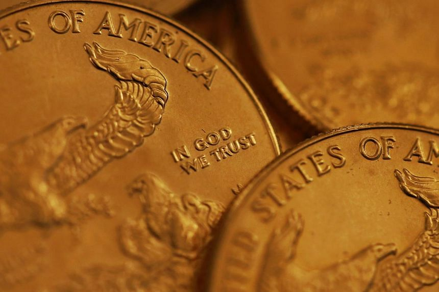 One ounce American gold coins in this arranged photograph. Gold has gained as investors assess the strength of the United States economy amid slumping oil prices. -- PHOTO: BLOOMBERG