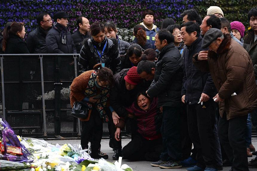 Family members mourning on Jan 6, 2015, for the victims of a new year's eve stampede at Shanghai's historic riverfront. -- PHOTO: AFP