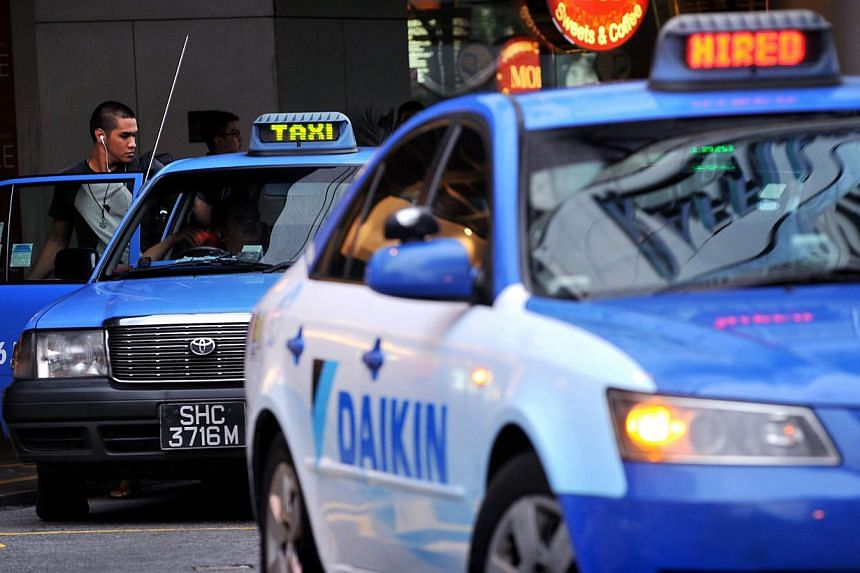 Passenger boarding a ComfortDelGro taxi. The largest taxi operator here clocked a record 35.6 million taxi bookings in 2014. -- ST PHOTO: NG SOR LUAN
