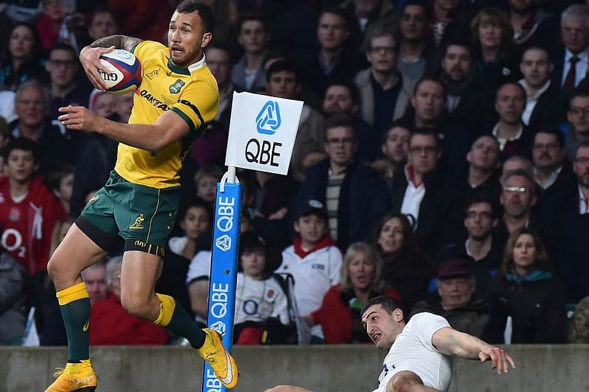 Australia's Quade Cooper (left) wins the ball from England's wing Jonny May (right) during the Autumn International rugby union Test match between England and Australia at Twickenham Stadium, southwest of London on Nov 29, 2014. Wallaby fly-half Quad