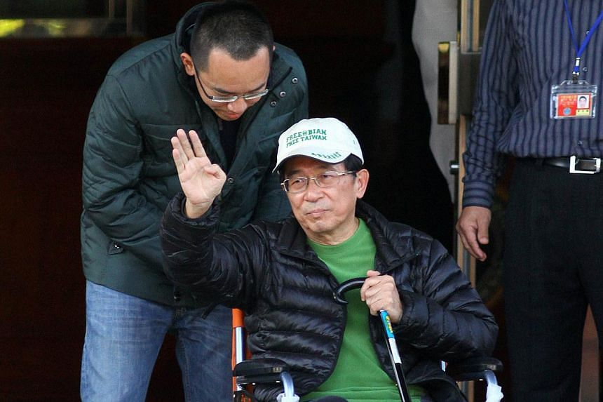 Former Taiwan president Chen Shui-bian (centre) waves to supporters as he is escorted by his son Chen Chih-chung (left) after being freed from prison in Taichung on Jan 5, 2015. Taiwanese prosecutors on Friday indicted convicted former president