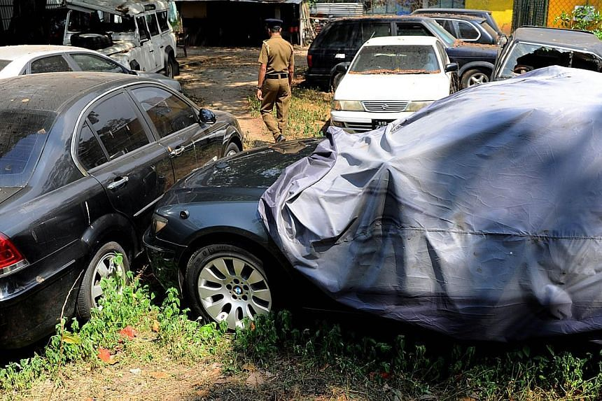A Sri Lankan police officer walks through a vehicle yard found in the capital Colombo on Jan 23, 2015.Sri Lanka's police Friday seized a fleet of more than 50 state-owned vehicles, including bullet-proof limousines, that were not returned after