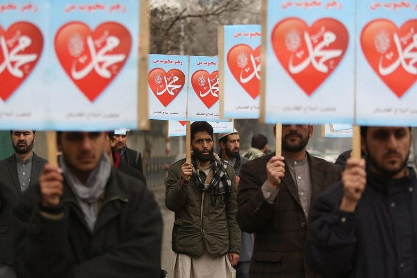 Afghan people hold placards reading in Arabic 'Prophet of God, peace be upon him', during a protest against the decision by the controversial French magazine 'Charlie Hebdo' to publish a depiction of the Prophet Muhammad, in Kabul, Afghanistan on Jan