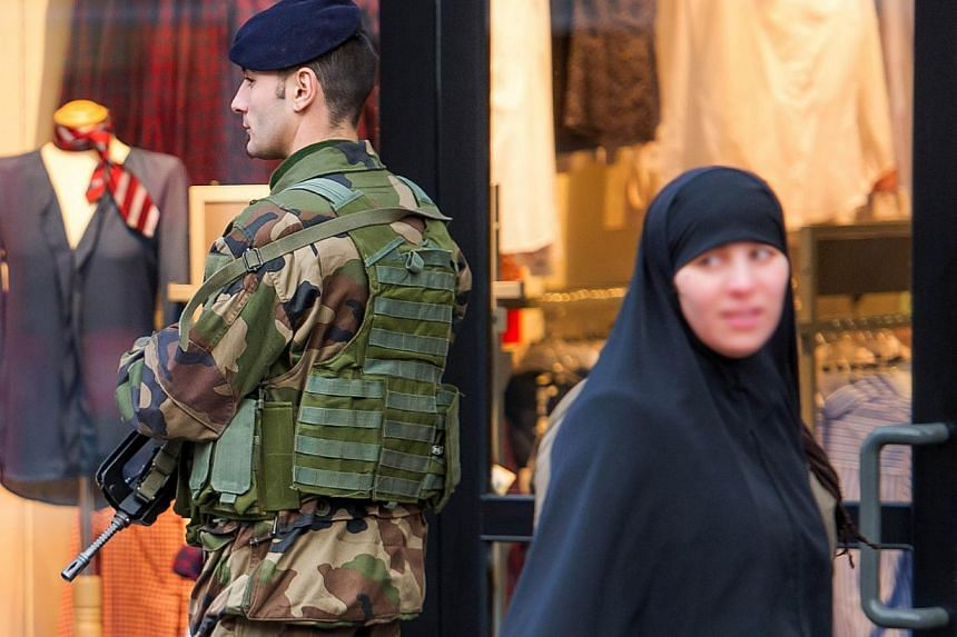 "A veiled woman walks past a soldier patroling in a street of Roubaix, northern France, on Jan 13, 2015, as France announced an unprecedented deployment of thousands of troops and police to bolster security at ""sensitive"" sites. -- PHOTO: AFP"
