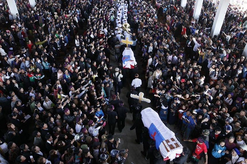 People attend a funeral service of two school teachers in Myitkyina, northern Myanmar on Jan 23, 2015. -- PHOTO: AFP