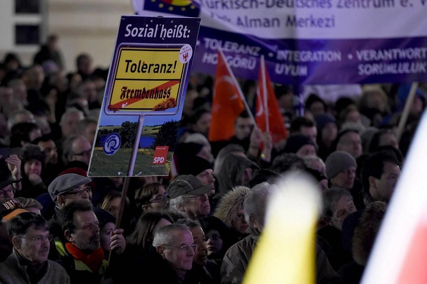"""A poster saying """"social means tolerance"""" at a Muslim community rally at Berlin's Brandenburg Gate last week to condemn the Paris attacks, urge tolerance and send a rebuke to a growing anti-Islamic movement."""