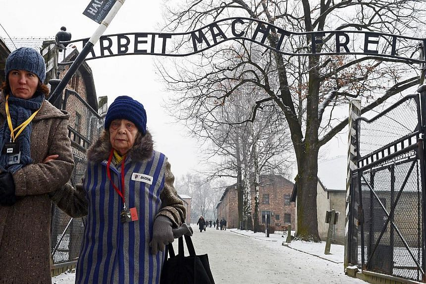 This photo taken on Jan 27, 2014, shows a former concentration camp prisoner attending (right) a ceremony at the memorial site of the former Nazi concentration camp Auschwitz-Birkenau in Oswiecim, Poland, on Holocaust Day. Polish officials said