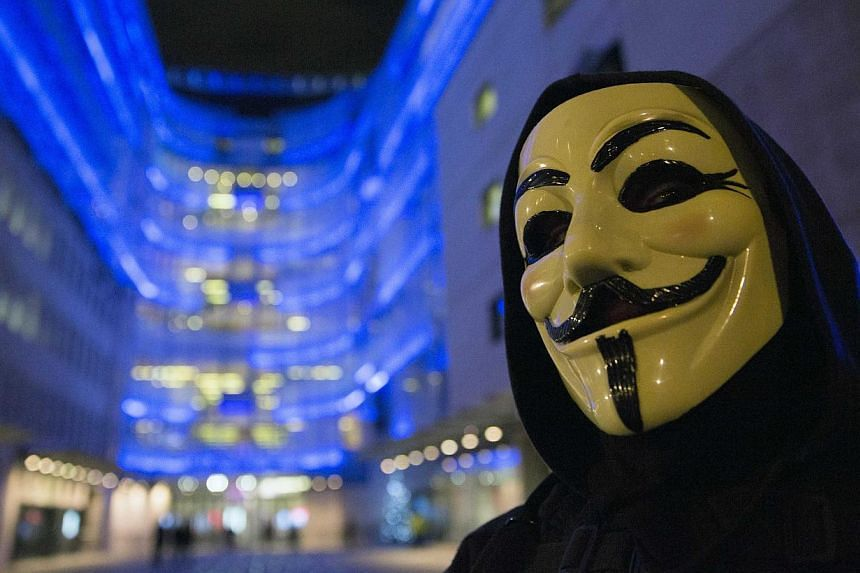 A supporter of the activist group Anonymous wearing a mask associated with the group on Dec 23, 2014. A journalist also known as an informal spokesman for the hacker group Anonymous was sentenced to five years in prison on Thursday in a case which ra