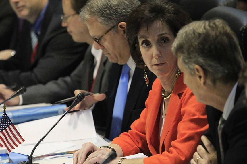 US assistant secretary of stateRoberta Jacobson (orange jacket) talks to deputy assistant secretary of state Alex Lee (second right) during negotiations to restore diplomatic ties with Cuba in Havana Jan 22, 2015. -- PHOTO: REUTERS