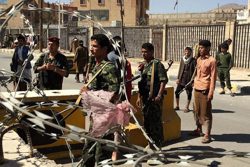 Shi'ite Huthi militiamen wearing uniforms confiscated from the Yemeni army stand at a barrier in the area around the house of the country's President in the capital Sanaa, on Jan 22, 2015. -- PHOTO: AFP