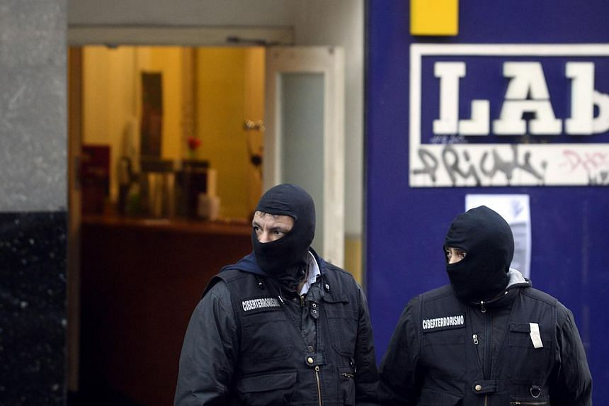 Spanish civil guards wearing uniforms of the cyber terrorism division stand guard outside the Lab Basque nationalist trade union during a police operation against suspected members of a support structure for Basque separatists ETA, in Bilbao Jan 12,