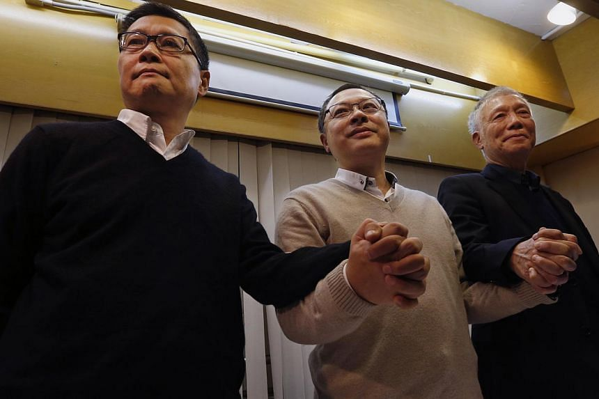 Hong Kong's original Occupy organisers Benny Tai (centre), Chan Kin Man (left) and Chu Yiu Ming joining hands during a news conference on their voluntary surrender to the police, on Dec 2, 2014. -- PHOTO: REUTERS
