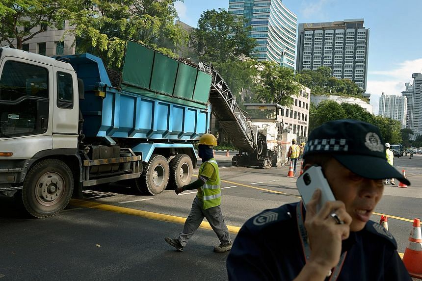 A policeman trying to handle traffic on the morning of Jan 15, 2015, as road resurfacing works were conducted along Paterson Road, adjacent to Orchard Boulevard, where an oil spill occurred earlier. -- PHOTO: ST FILE