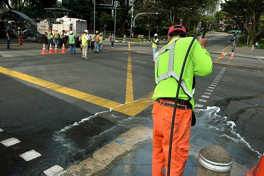 A cleaner washing the pavement at the junction of Paterson Road and Orchard Boulevard. Road resurfacing works were conducted along Paterson Road, adjacent to Orchard Boulevard, where an oil spill occurred in the early hours of Jan 15, 2015. -- PHOTO: