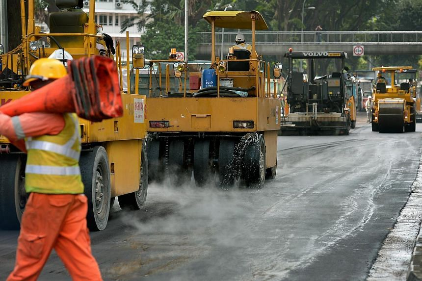 Road resurfacing works being conducted along Paterson Road, adjacent to Orchard Boulevard, where an oil spill took place in the early hours of Jan 15, 2015. -- PHOTO: ST FILE