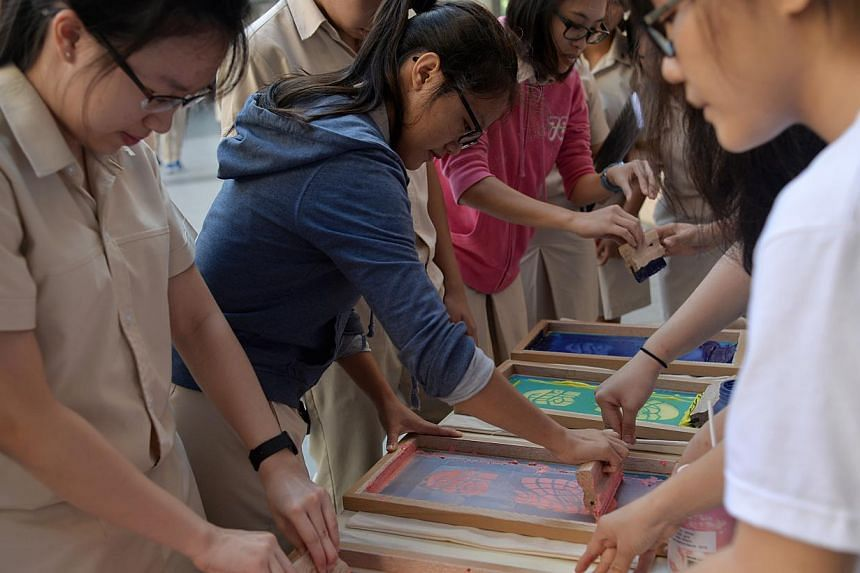 Hwa Chong students making silkscreen prints on bags with help from SUTD students who dropped by to talk about their projects.