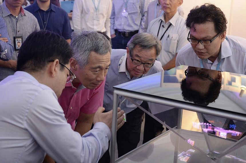 PM Lee takes a close look at a 3D holographic display system prototype with (from left) Spectral Reality director Bernard Song, JTC Corporation chairman Loo Choon Yong and Rock Nano Global CEO Ang Chong Lai.