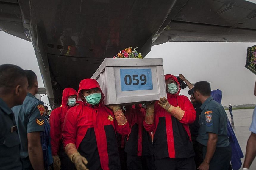 Indonesian rescue personnel unloading a coffin bearing a body recovered from the underwater wreckage of AirAsia flight QZ8501 from a military plane on arrival at Surabaya on Jan 23, 2015. Salvage teams on Jan 24 launched an operation to raise the pla