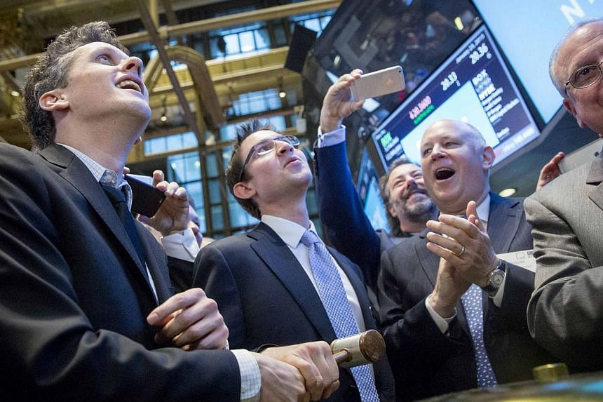 Box co-founder and chief executive Aaron Levie (left) and co-founder and chief financial officer Dylan Smith (second left) ring a ceremonial bell during their company's IPO on the floor of the New York Stock Exchange Jan 23, 2015. -- PHOTO: REUTERS