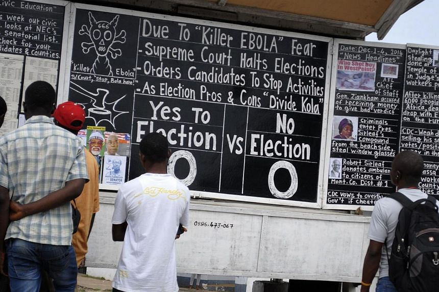 Bystanders read the headlines illustrating the battle over the holding of elections in Liberia amid the Ebola crisis at a street side chalkboard newspaper in Monrovia, Dec 2, 2014. -- PHOTO: REUTERS
