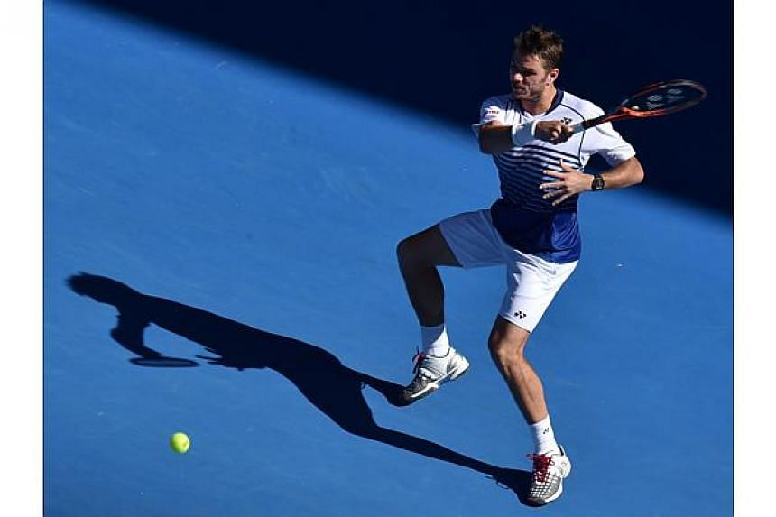 Stan Wawrinka of Switzerland hits a return against Jarkko Nieminen of Finland during the men's singles on day six of the 2015 Australian Open tennis tournament in Melbourne on Jan 24, 2015. -- PHOTO: AFP