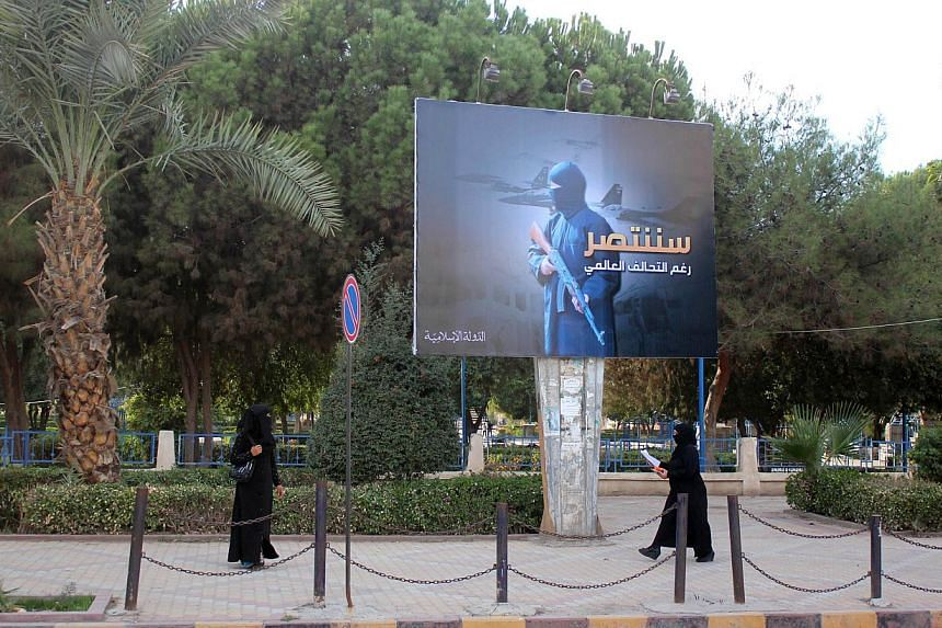 Women wearing a niqab, a type of full veil, walk under a billboard erected by ISIS as part of a campaign in the ISIS controlled Syrian city of Raqqa on Oct 1, 2014. -- PHOTO: AFP