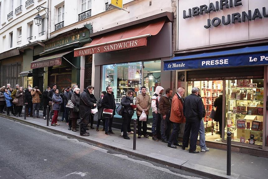 People waiting outside a newsagents in Paris on Jan 14, 2015 as the latest edition of French satirical magazine Charlie Hebdo goes on sale. -- PHOTO: AFP
