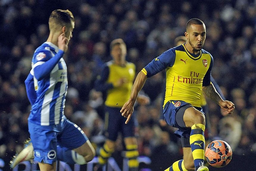 Arsenal's Theo Walcott (right) in action against Brighton's Joe Bennett during the FA Cup fourth round at the American Express Community Stadium in Brighton on Jan 25 2015. -- PHOTO: EPA