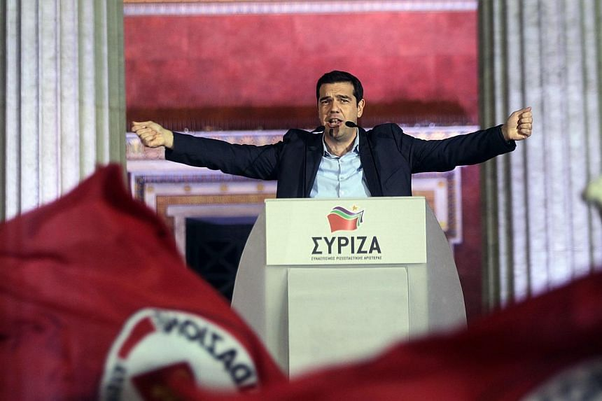 Alexis Tsipras, opposition leader and head of the radical leftist Syriza party, greeting supporters after the initial election results for the Greece general elections in Athens on Jan 25 2015. -- PHOTO: EPA