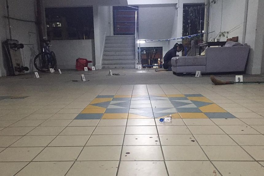Bloodstains are seen on the floor near where a man attacked two neighbours with a parang. -- ST PHOTO: MELODY ZACCHEUS